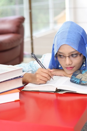 A muslim woman reading a book while looking at the book on the table photo