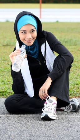 hacer footing: Una hermosa mujer musulmana atleta en reposo, mientras que beber un agua mineral