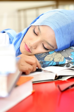 A young muslim woman sleeping while reading a book