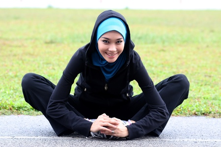 A pretty muslim woman athlete stretching her body at stadium track photo