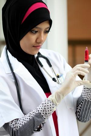 chemist: A pretty muslim woman doctor checking syringe