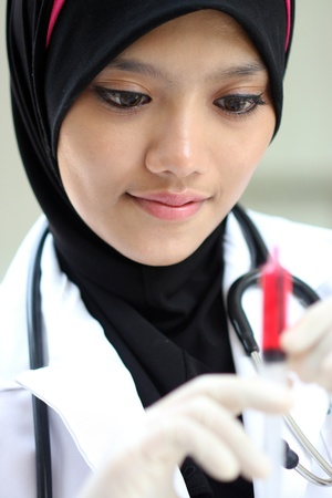 A portraits of pretty muslim woman doctor checking syringe Imagens