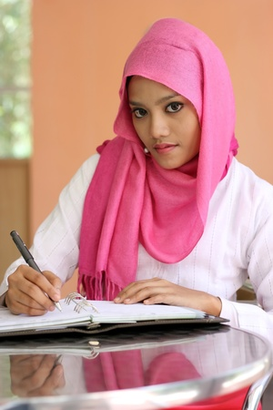 learning by doing: A beautiful muslim girls writing a diary book on the table