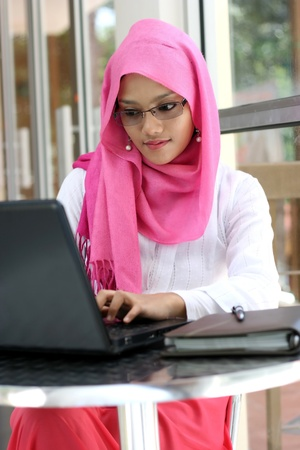 A young muslim woman using laptop  photo