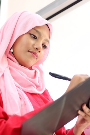 A young beautiful muslim girl writing on report file photo