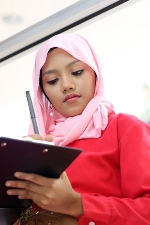 A young beautiful muslim girl writing on report file Imagens