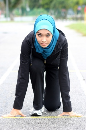 Athletic muslim woman on track starting to run  Imagens