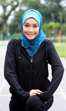 femmes muslim: Un athlète jolie femme musulmane qui s'étend, dans l'exercice