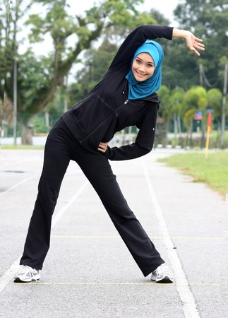 A beautiful muslim woman athlete stretching her body at stadium track