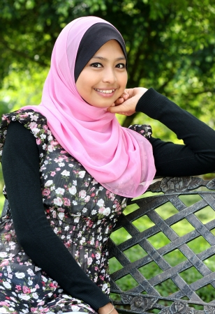 femmes muslim: Jeune femme musulmane est assis sur le banc en automne parc et regardant la caméra
