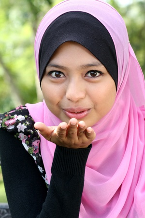 Portrait of cute young muslim female blowing kiss photo