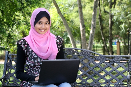 Beautiful muslim woman using laptop while sitting relaxed on bench at summer park  Imagens