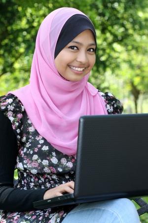 femme musulmane: Belle femme musulmane utilisant un ordinateur portable alors qu'il �tait assis sur le banc d�tendue au parc d'�t�