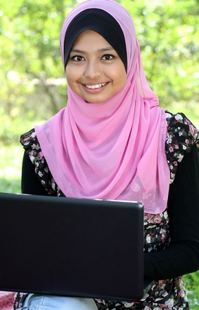 Beautiful muslim woman using laptop while sitting relaxed  at summer park