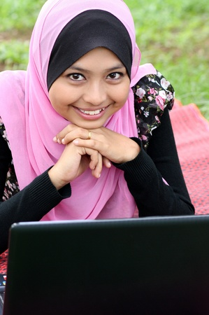 Portrait of young pretty muslim woman resting on mat at summer park using laptop  photo
