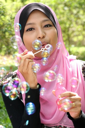 Young  pretty muslim girl inflating colorful soap bubbles  photo
