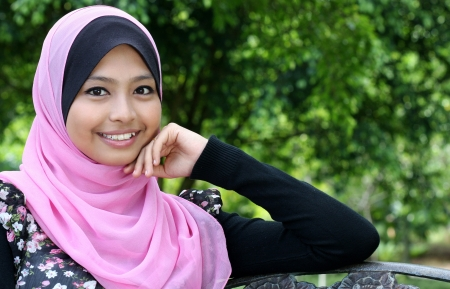 muslim woman: young woman is sitting on the bench in autumn park and looking at camera  Stock Photo