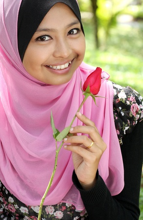 Portrait of beautiful young muslim girl holding a red rose flower at park photo