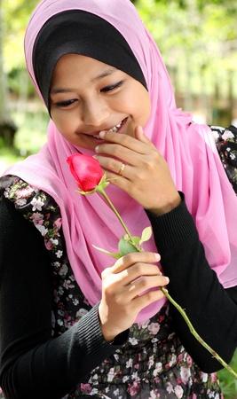 femmes muslim: Portrait de la belle jeune fille musulmane de jeunes tenant une rose rouge fleur au parc