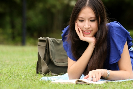 Pretty young woman reading her book at park.