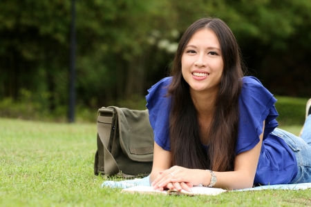 Pretty young woman reading a book at park with smile