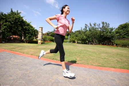 asian sport: Pretty woman running outdoors training at park Stock Photo