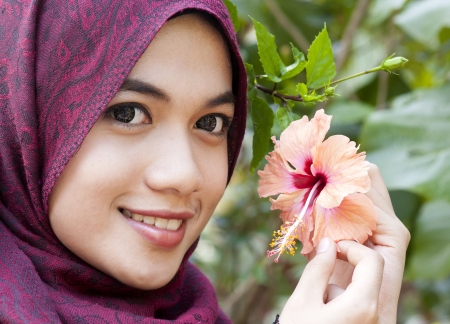 Young muslim woman holding a red hibiscus flower next to her face