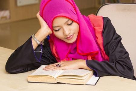 Portrait of muslim girl reading book  photo
