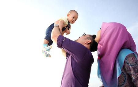 familias felices: Familia asi�tica que disfruta de tiempo de calidad en la playa con el padre, madre e hijo Foto de archivo