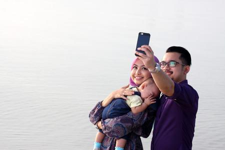 petite fille musulmane: Belle famille � la plage faire un autoportrait avec un t�l�phone mobile Banque d'images