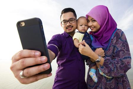 携帯電話で自己の肖像画を作ってビーチに美しい家族