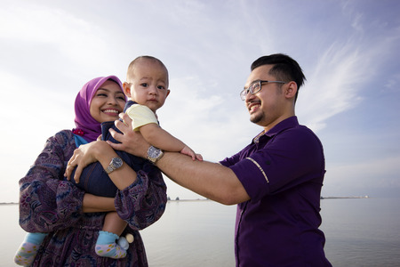 indonesia girl: Asian family enjoying quality time on the beach
