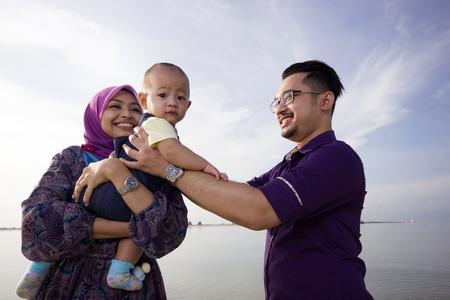 familias jovenes: Familia asi�tica que disfruta de tiempo de calidad en la playa Foto de archivo