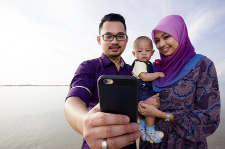 camera girl: Beautiful family at beach making a self portrait with a mobile phone