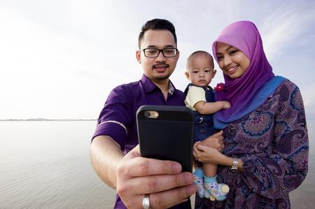 petite fille musulmane: Belle famille à la plage faire un autoportrait avec un téléphone mobile Banque d'images