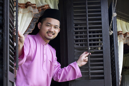 Malay muslim man open a traditional window house