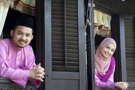 Malay muslim couple with greeting hari raya.