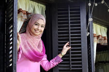 personas saludandose: Mujer musulmana malaya en la casa tradicional ventana