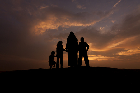 during: silhouettes of a muslim women with her kid during sunset