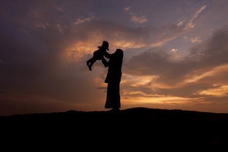 silueta niño: Silueta de la madre que da vuelta al niño contra una puesta de sol Foto de archivo