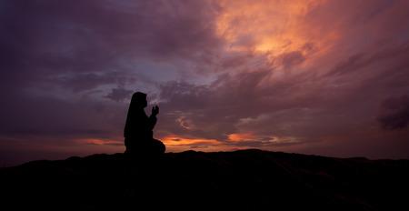 mujeres orando: siluetas de las mujeres musulmanes orar durante la puesta del sol
