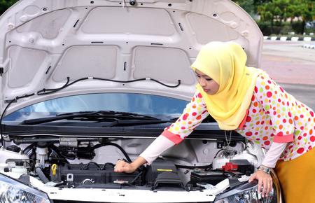 Jeune femme musulmane moteur vérifier sur sa voiture