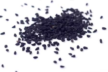 Black seeds isolated on white with shallow depth of field