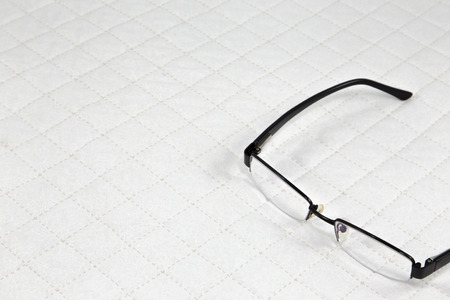 patchwork quilt: eyeglasses put on white patchwork Quilt background