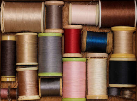 Assorted sewing thread on a wooden background Imagens
