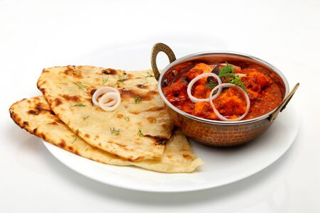 Indian Food or Indian Curry in a copper brass serving bowl with bread or roti. Standard-Bild