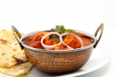 Indian Food or Indian Curry in a copper brass serving bowl with bread or roti.