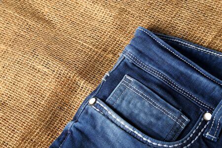 Old Blue jeans fashion design On brown hemp sack texture background,.Ripped jeans of a stack Hipster fashion copy space for text commentary .