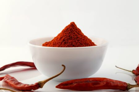 Red chillies with red chilly powder on white background. Imagens