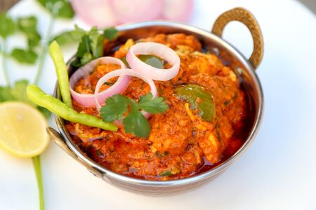 INDIAN STYLE COTTAGE CHEESE VEGETARIAN CURRY DISH. Kadai Paneer - Traditional Indian or Punjabi food. Garnished with onion and chili slices. Stock Photo